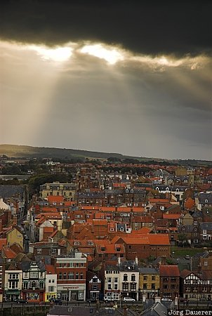 Clouds above Whitby, United Kingdom, Whitby, Yorkshire, clouds, dark clouds, evening light, houses, sun beams, North Yorkshire